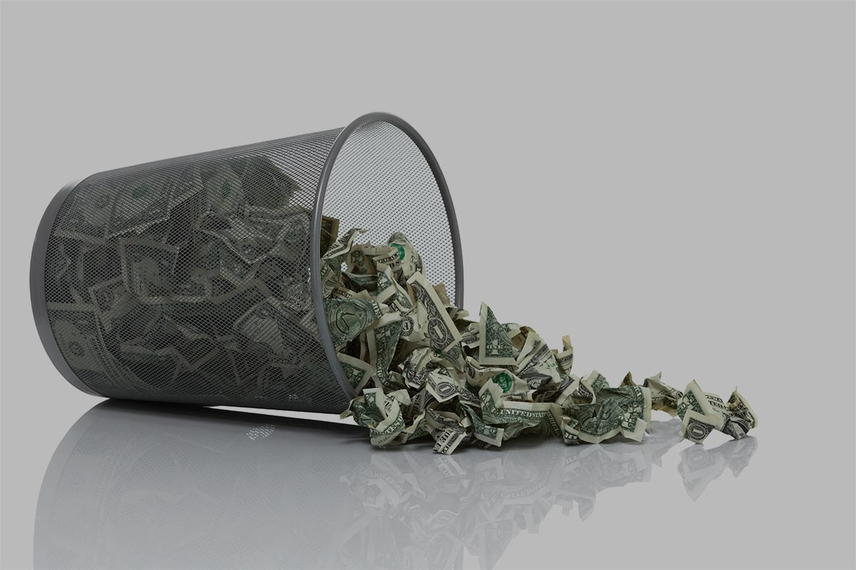 Garbage can full of money tipped on its side with money spilling out