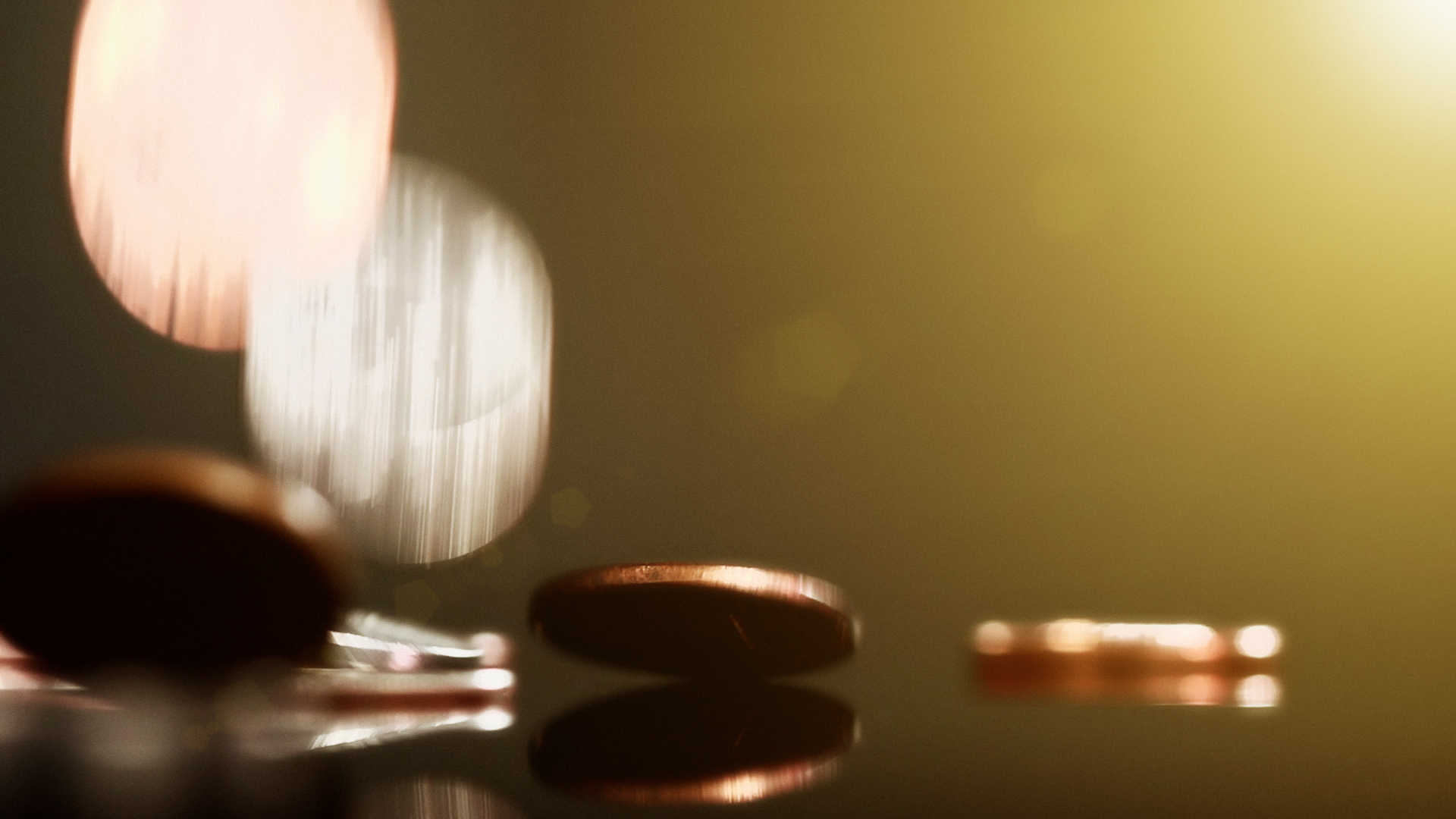 Silver and copper coins falling onto a reflective surface, showing  motion blur and lens flare. Copy space on the greeny-gold background.